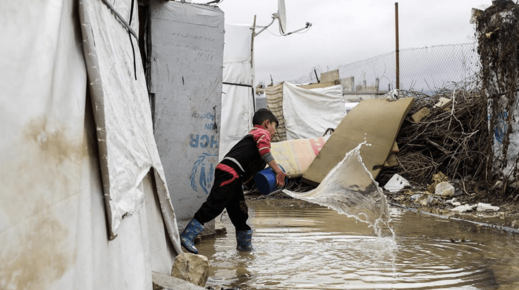 A Syrian child uses a bucket to bale out water from his tent at a refugee camp on the outskirts of the town of Zahle in Lebanon's Bekaa Valley. Joseph Eid / AFP